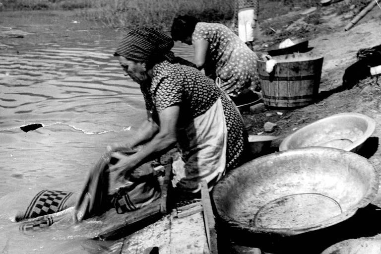Lavadeiras lavam roupas à beira do Rio Tietê, em São Paulo