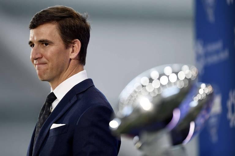 Manning, de terno, morde os lábios ao lado de troféus