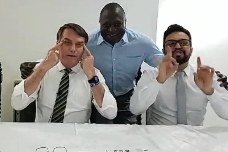 Em live, Bolsonaro puxa as pálpebras para imitar formato do olho dos orientais, enquanto faz piada acompanhado do deputado Hélio Lopes (centro)