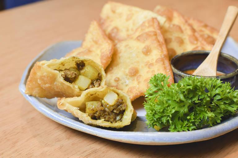 Telma Shiraishi, do Aizomê, comemora o aniversário de São Paulo com porções de pastéis como esta, recheada de carne, legumes e karê; quitute está no menu do Aizomê da Japan House