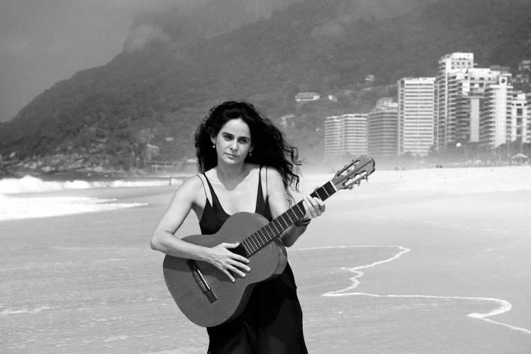 mulher com vestido preto na praia