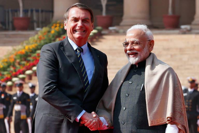 À esquerda, presidente Jair Bolsonaro sorri e olha para foto. ele usa a mão direita para cumprimentar o primeiro-ministro indiano, Narendra Modi, que sorri