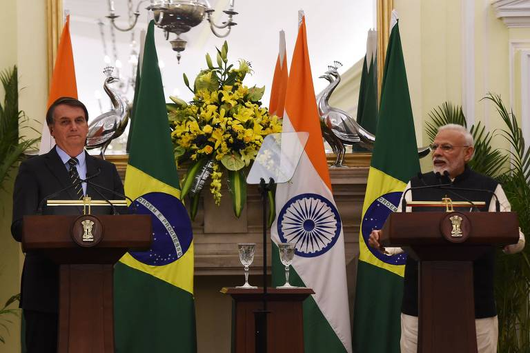 Jair Bolsonaro (à esquerda) ouve fala de Narendra Modi (à direita). Ambos estão atrás de púlpitos. Atrás deles estão as bandeiras de Brasil e Índia.