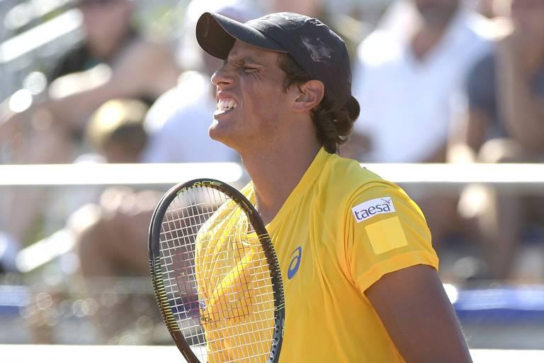 Tenista João de Souza comemora vitória. Ele tem as duas mãos fechadas, na esquerda segura a raquete. Usa boné azul e camisa amarela.