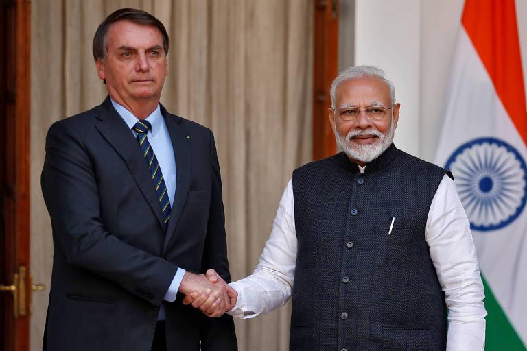 Jair bolsonaro, à esquerda, e Narendra Modi, à direita, apertam as mãos em cumprimento e posam para foto