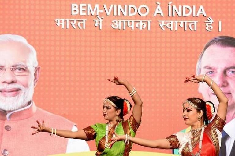 """Dançarinas performam. Ao fundo, cartaz com o texto """"bem vindo à Índia"""". Ao lado esquerdo, no cartaz, o primeiro-ministro indiano, Narendra Modi. Ao lado direito, o presidente Jair Bolsonaro"""