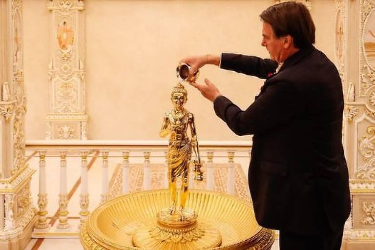 O presidente Jair Bolsonaro joga água sobre uma escultura dourada
