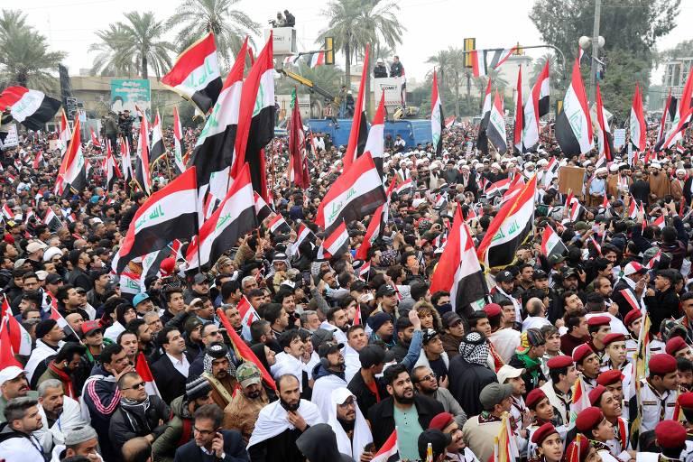 Centenas de pessoas aglomeradas a céu aberto e várias delas com bandeiras do Iraque levantadas
