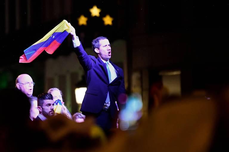 Líder opositor venezuelano Juan Guaidó com bandeira de seu país durante ato em Madri