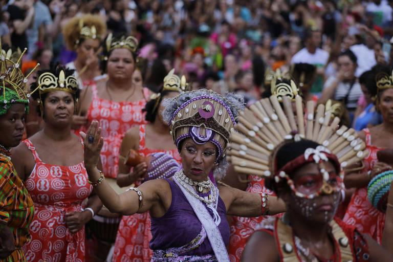 Mulheres vestidas com trajes e adereços da tradição afro-brasileira fazem coreografia em meio a multidão