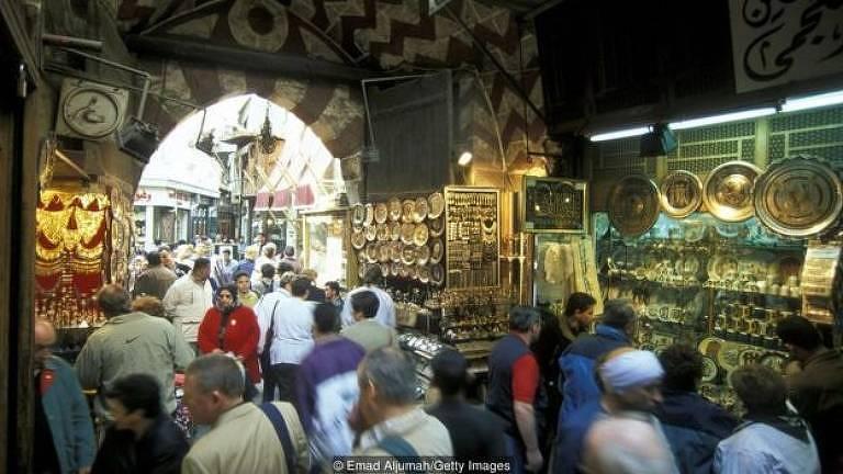 Mercado com peças de ouro e muitas pessoas dentro