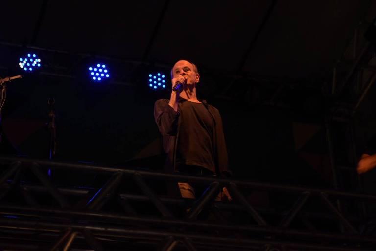 homem em cima do palco com microfone em mãos