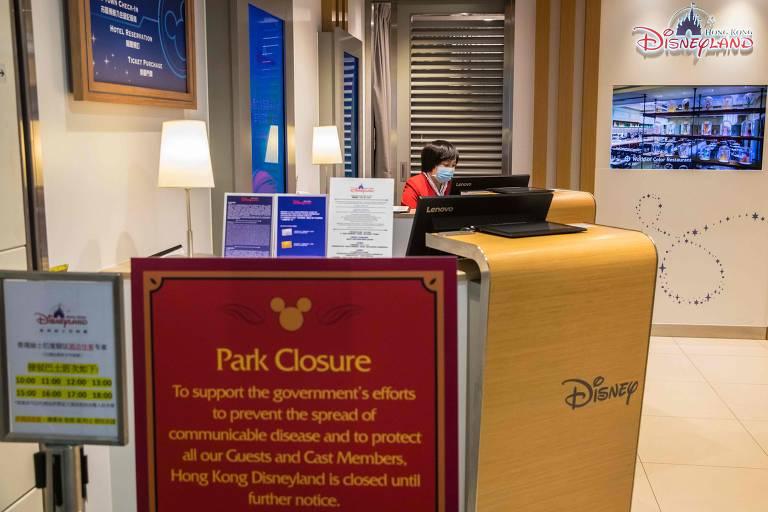 Imagem mostra funcionário usando uma máscara dentro de um escritório de ingressos da Disneyland, em estação de trem de alta velocidade em Hong Kong