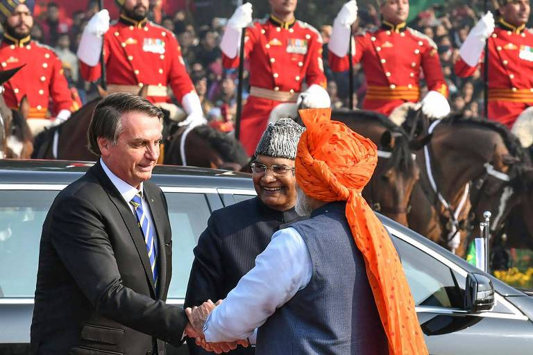 de terno, à esquerda, Jair Bolsonaro cumprimenta o primeiro-ministro indiano Narendra Modi, que usa traje nas cores branco e colete azul, com um turbante laranja na cabeça que tem um longo tecido que cai pelas costas do premiê. Atrás deles, em segundo plano, soldados com uniformes vermelhos estão em posição de sentido durante parada militar
