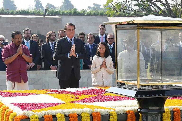 Jair Bolsonaro, acompanhado por um homem de camisa vermelha e uma criança com roupas brancas, presta homenagem a memorial de Gandhi, que está decorado com pétalas de diferentes cores. Todos têm as mãos unidas pelas palmas em gesto de prece.
