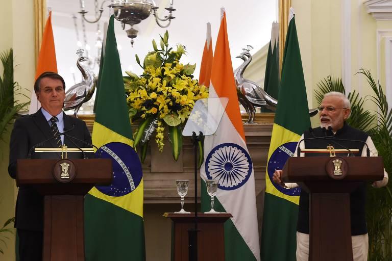 jair bolsonaro e narendra modi, à esquerda e à direita, respectivamente, estão atrás de púlpitos. ao fundo estão as bandeiras do Brasil e da Índia