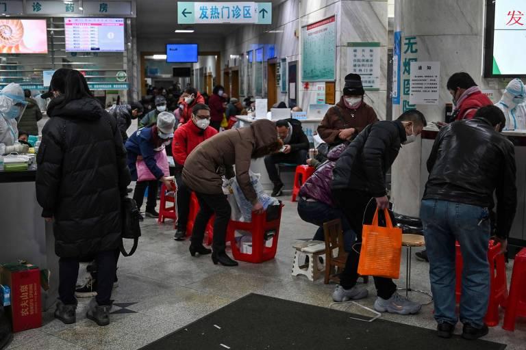 Pessoas fazem fila à espera de atendimento médico no hospital da Cruz Vermelha em Wuhan, na China