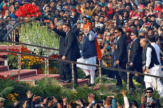 India's Prime Minister Narendra Modi waves next to Brazil's President Jair Bolsonaro and India's President Ram Nath Kovind as they arrive to attend India's Republic Day parade in New Delhi