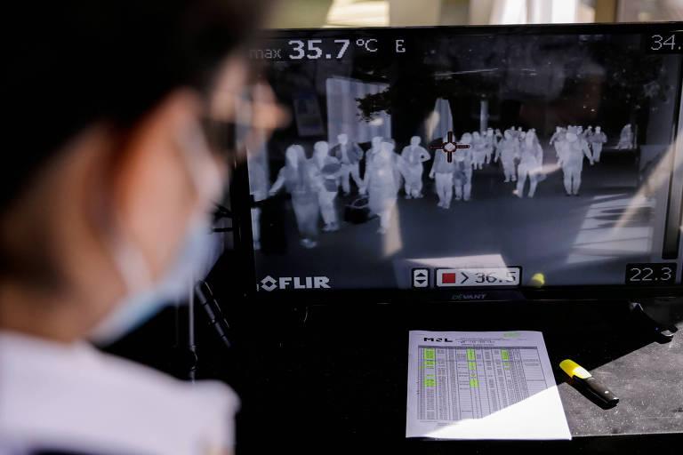 Funcionária do Aeroporto Internacional Ninoy Aquino, nas Filipinas, monitora scanner termal para identificar passageiros com sintomas de infecção pelo coronavírus