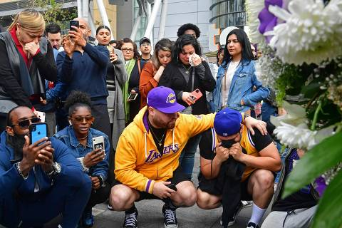 People gather around a makeshift memorial for former NBA and Los Angeles Lakers player Kobe Bryant after learning of his death at LA Live plaza in front of Staples Center in Los Angeles on January 26, 2020. - NBA legend Kobe Bryant died January 26, 2020 in a helicopter crash in suburban Los Angeles, celebrity website TMZ reported, saying five people are confirmed dead in the incident. (Photo by Frederic J. Brown / AFP)