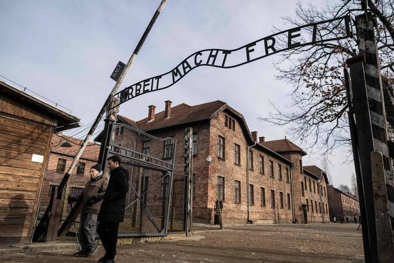 Ex-prisioneiro de Auschwitz, à esq., atravessa portão de entrada do campo de concentração em Oswiecim com a inscrição 'o trabalho liberta'