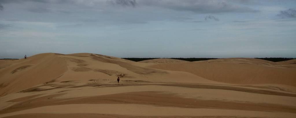 Mulher caminha ao longe sobre uma paisagem toda de dunas