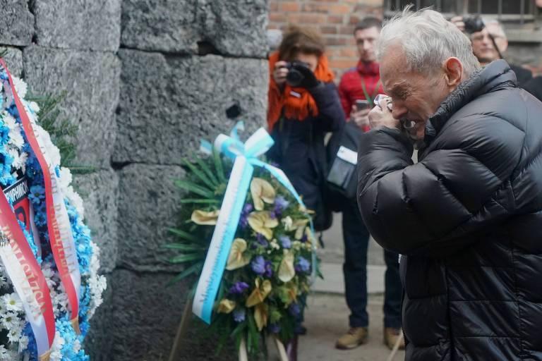 Sobrevivente do Holocausto chora após depositar flores em memorial às vítimas do nazismo em Auschwitz