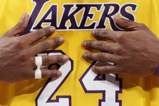 Lakers' Bryant displays his injured pinkie finger during their NBA game against the Heat in Los Angeles