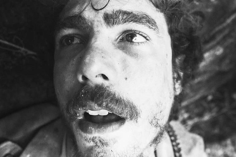 Homem com expressão de delírio em fotografia preto-e-branca