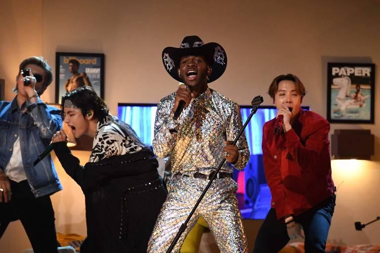 Três jovens asiáticos cantam ao lado de um homem negro com roupas prateadas no estilo caubói