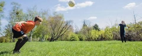 Criança se prepara para cabecear a bola em atividade recreativa