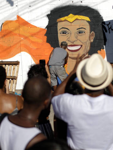 Street artist Aira Ocrespo paints a graffiti art in tribute of Rio de Janeiro city councilor Marielle Franco in Mare slums complex, which was her home community, during a rally in Rio de Janeiro, Brazil March 18, 2018.  REUTERS/Ricardo Moraes ORG XMIT: RJO12