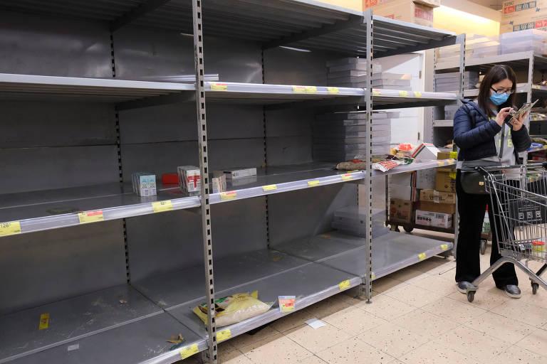 Cliente em supermercado com prateleiras vazias em Hong Kong, na China