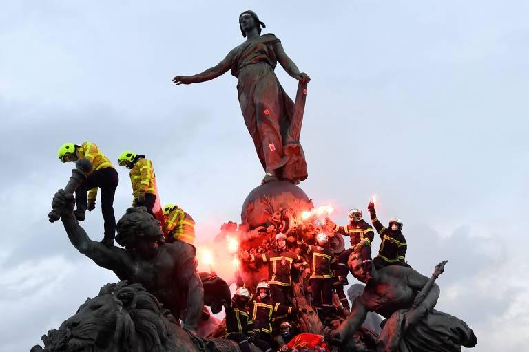 Bombeiros parisienses sobem na estátua do Triunfo da República durante manifestação