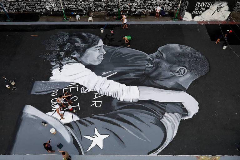 Fãs fazem o polimento de desenho em uma quadra de basquete nas Filipinas, feito em homenagem a Kobe Bryant e a filha Gianna, mortos no domingo (26)