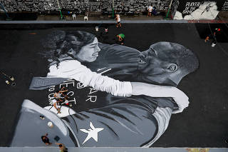 Fans polish the mural in memory of Kobe Bryant and his daughter Gianna