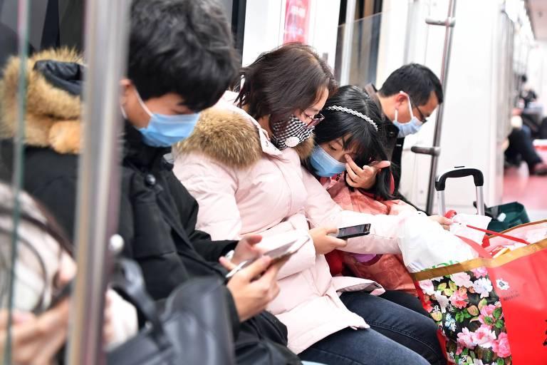 Retrato de quatro pessoas sentadas em um vagão de metrô; todas usam máscaras no rosto e olham para o celular