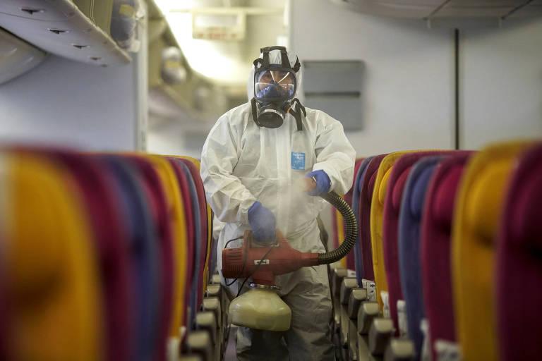 Um membro da tripulação da Thai Airways desinfeta a cabine de uma aeronave para impedir a propagação do coronavírus no Aeroporto Internacional de Suvarnabhumi, em Bangcoc, na Tailândia