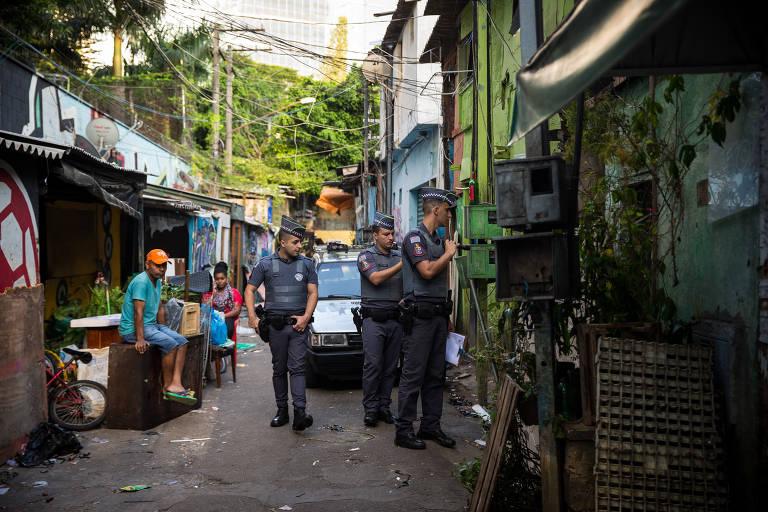 três policiais andam em viela enquanto são observados por moradores