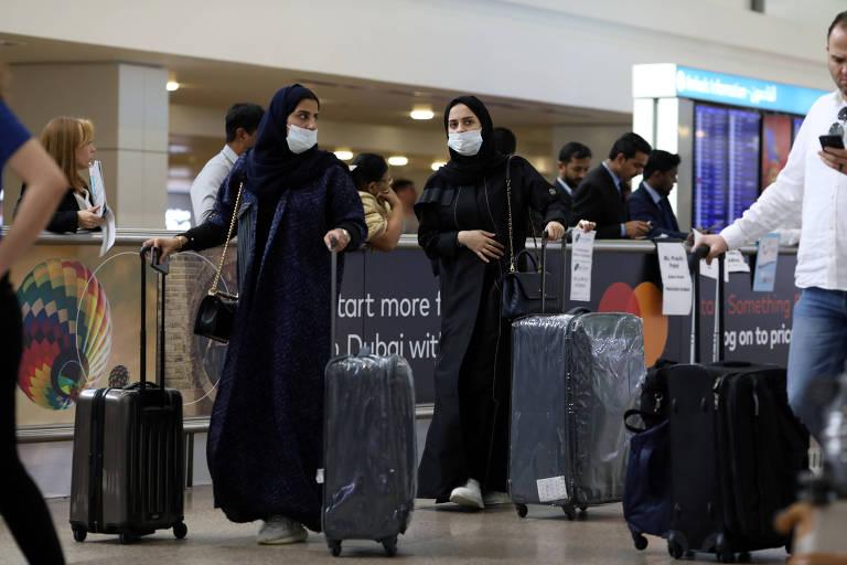 Pessoas usam máscaras ao chegar no aeroporto internacional de Dubai depois que o país confirmou os primeiros casos de coronavírus