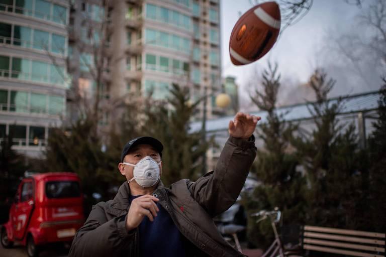 Um homem joga futebol americano com máscara, nas ruas de Pequim, na China