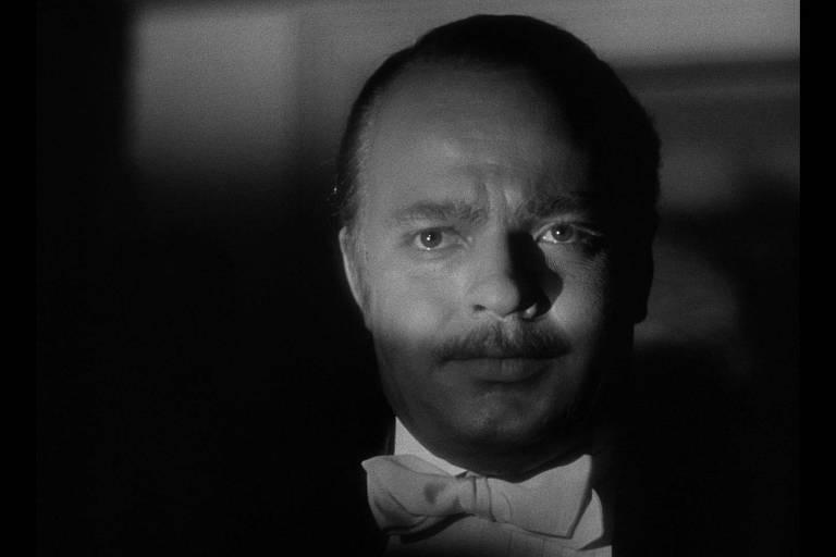 O magnata Kane olha para frente e apenas os seus olhos estão iluminados. Seu olhar é de profunda angústia.