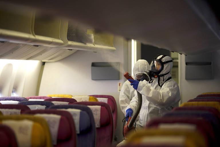 Tripulação da Thai Airways desinfeta cabine de aeronave por causa do surto de coronavírus
