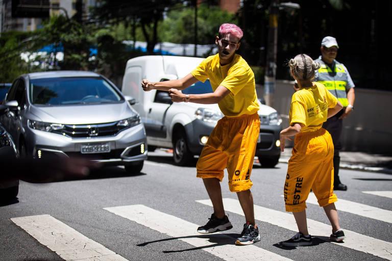 Homem e mulher vestidos de amarelo e com rosto pintados simulam com gestos condução de motocicleta em cima de uma faixa de pedestre, diante da qual dois carros e um fiscal de trânsito com colete e boné aguardam