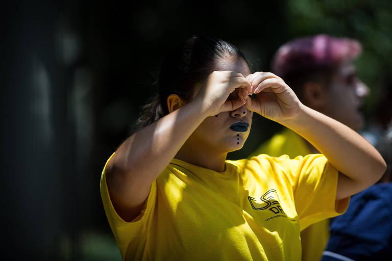 Mulher vestida de camiseta amarela com as letras CET e rosto pintado faz gesto circular com as mãos imitando um binóculo