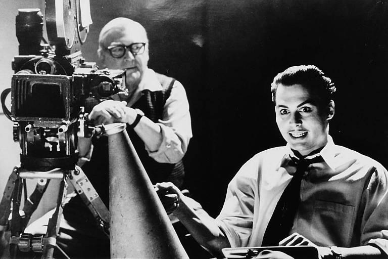 O diretor do filme está sentado em sua cadeira no set de filmagem, ele tem um sorriso estranho, um pouco maníaco, enquanto o câmera o encara atrás do equipamento