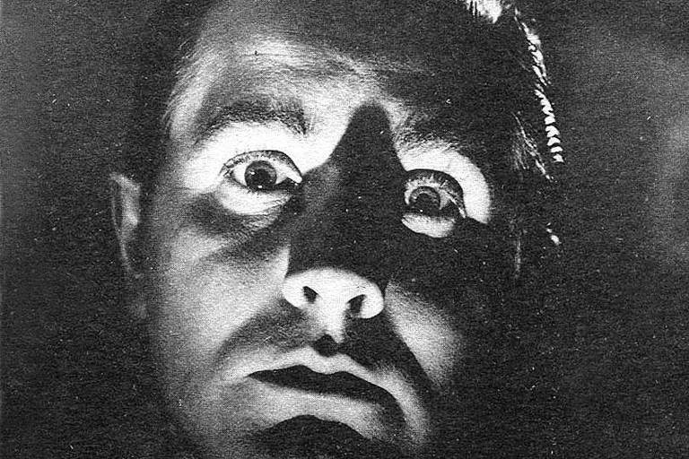 Fotografia em preto e branco do cineasta Ed Wood. Ele encara a câmera de frente e tem olhos esbugalhados, além do rosto em meia luz