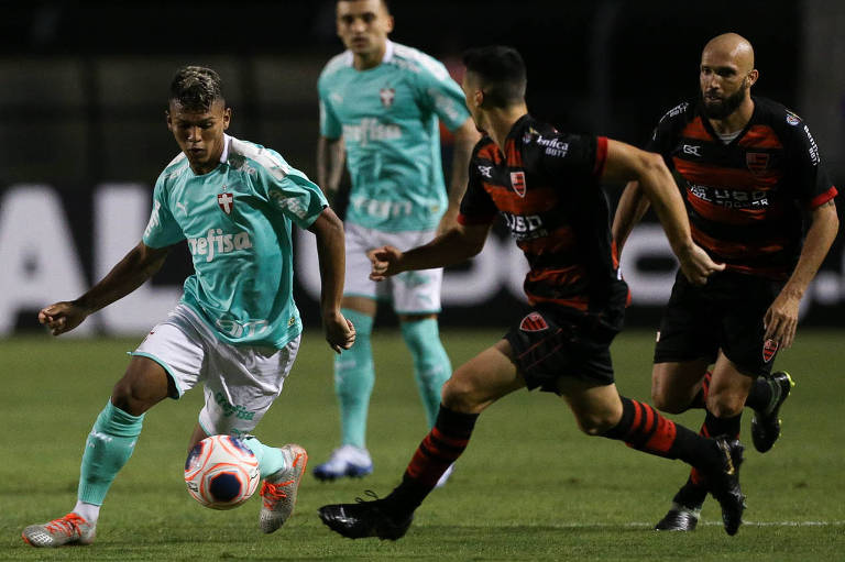 O jogador Gabriel Veron, da SE Palmeiras, disputa bola com o jogador Eder Sciola, do Oeste FC, durante partida válida pela terceira rodada, do Campeonato Paulista, Série A1, no Estádio do Pacaembu.