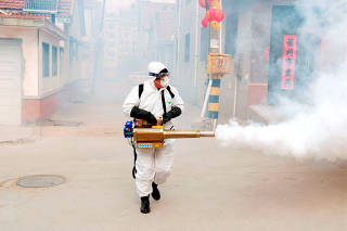 Worker in protective suit disinfects the Dongxinzhuang village, as the country is hit by the new coronavirus, in Qingdao