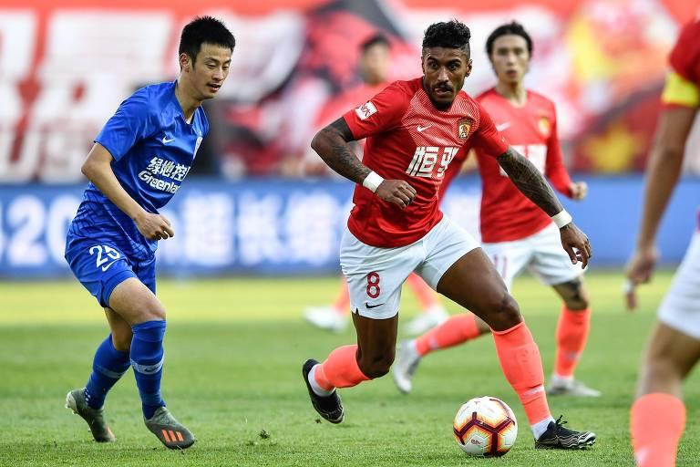 O brasileiro Paulinho (de vermelho) em ação pelo Guangzhou Evergrande, atual campeão chinês